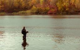 Fischerfischen, das im Wasser steht Lizenzfreie Stockbilder