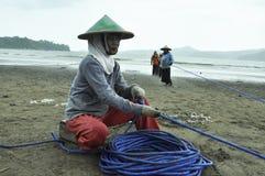 Fischerfrau bei der Arbeit, welche die Seilnetze zieht Stockbild