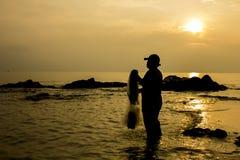 Fischergrifffischnetz am Morgen; Schattenbildart Lizenzfreie Stockbilder