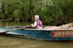 Fischerin handhabt ein Boot mit Rudern auf der Donau stockbild
