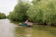 Fischerin handhabt ein Boot mit Rudern auf der Donau lizenzfreie stockbilder