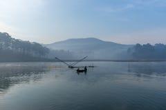 Fischermannreihe das Boot auf dem See das Werkzeug des Fischermannes, sie unter Verwendung dieses für ihren Job, im nebeligen Lizenzfreie Stockfotos