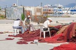 Fischermen che ripara le loro reti in un porto di Corfù Immagini Stock Libere da Diritti