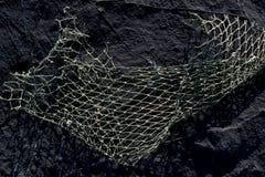 Fischernetz auf einem Felsen als Hintergrundbeschaffenheit lizenzfreies stockbild