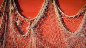 Fischernetz, das an der roten Wand hängt Lizenzfreies Stockbild