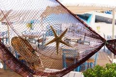 Fischernetz verziert mit Starfish und Muschel am traditionellen griechischen Restaurant durch Strand und Fischereihafen Stockbilder