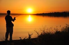 Fischerschattenbild auf Sonnenunterganghintergrund in den Schatten des Gelbs Stockbilder