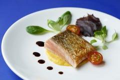 Fischfilet auf einer Platte mit Tomaten und Kopfsalat Stockfotos