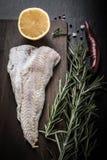Fischfilet, Rosmarin, Pfeffer des roten Paprikas, Hälfte Zitrone und Seesalz Stockbild
