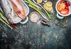 Fischgerichte, die Vorbereitung mit rohen ganzen Forellenfischen und Goldregenbogenforelle und Bestandteile auf dunklem rustikale Lizenzfreies Stockfoto