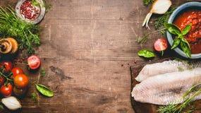 Fischgerichtkochen Frisches rohes Fischfilet mit Tomaten, Soße und Bestandteilen auf rustikalem hölzernem Hintergrund, Draufsicht Lizenzfreies Stockfoto