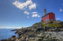 Fisgard Lighthouse. Canadian National Historic Site Fisgard Lighthouse on Pacific Coast. Small cruise ship on horizon Royalty Free Stock Photography