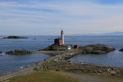 Fisgard lighthouse. Lighthouse stands on spit under cloudy sky Royalty Free Stock Photo
