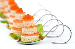 Fish appetizers. Tidbits with smoked salmon, caviar, cream cheese and toast on party spoons Royalty Free Stock Photo