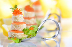 Fish appetizers. Tidbits with smoked salmon, caviar, cream cheese and toast on party spoons, lemons in the background Stock Images
