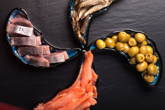 Fish assortment and olives on magic plates on a dark background Royalty Free Stock Photos