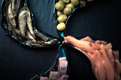 Fish assortment and olives on magic plates on a dark background Stock Photo