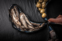 Fish assortment and olives on magic plates on a dark background Royalty Free Stock Photo