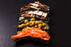 Fish assortment and olives on a plate on a dark background. With. Space for text Stock Photos