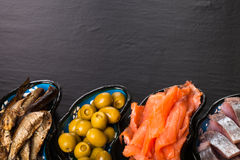 Fish assortment and olives on a plate on a dark background. With Stock Photography