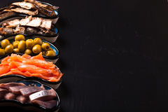 Fish assortment and olives on a plate on a dark background. With. Space for text Royalty Free Stock Photography