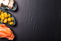 Fish assortment and olives on a plate on a dark background. With Royalty Free Stock Images