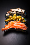 Fish assortment and olives on a plate on a dark background. With. Space for text Stock Images