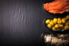 Fish assortment and olives on a plate on a dark background. With Stock Photo