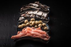 Fish assortment and olives on a plate on a dark background. With Royalty Free Stock Photography
