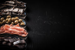 Fish assortment and olives on a plate on a dark background. With. Space for text Stock Photo