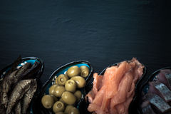 Fish assortment and olives on a plate on a dark background. With. Space for text. tinted Royalty Free Stock Photo