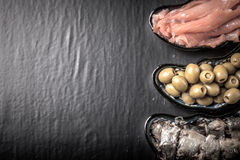 Fish assortment and olives on a plate on a dark background. With. Space for text. tinted Stock Photos