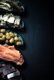 Fish assortment and olives on a plate on a dark background. With Royalty Free Stock Photo