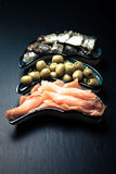 Fish assortment and olives on a plate on a dark background. With. Space for text. tinted Stock Images