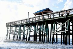 The fish are attracted to the pier which brings the osprey. Sunrise shines a light upon an old public fishing pier along the Atlantic Ocean seaboard stock photos