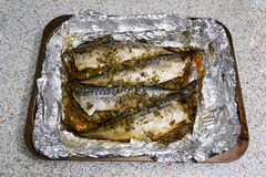 Fish baked in foil. Fish stuffed with spices, baked in foil on a baking sheet Royalty Free Stock Photo