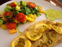 Fish baked in the oven with lemon and vegetable salad . Stock Image