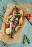 Fish baked in paper with vegetables on vintage wooden table Royalty Free Stock Image