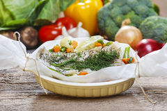 Fish in baking paper. Fresh vegetables in the background Royalty Free Stock Images