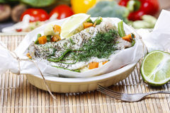 Fish in baking paper. Fresh vegetables in the background Stock Image