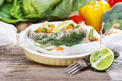 Fish in baking paper. Fresh vegetables in the background Royalty Free Stock Image
