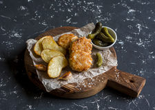 Fish balls and baked potatoes on wooden cutting board Royalty Free Stock Photo