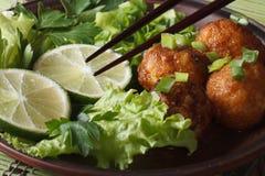 Fish balls with lime and salad and chopsticks macro. Horizontal Stock Photography