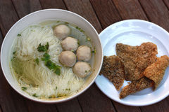Fish balls noodles served with fried fish skin. Fish balls clear soup noodles served with deep fried salmon fish skin Royalty Free Stock Image