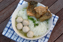 Fish balls noodles topped with fried fish skin. Fish balls clear soup noodles served with deep fried salmon fish skin Royalty Free Stock Image