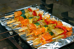 Fish on the barbecue. Delicious fish on sticks being grilled on a foil wrapped barbecue stock photo