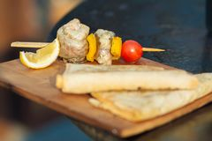 Fish barbecue. With cherry tomato and lemon on wooden cutting board stock image