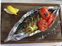 Fish barbeque wrapped in thee foil, healthy food. stock photos