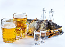 Fish, beer mugs and dried fish. Still life with fish, beer mugs and dried fish royalty free stock images