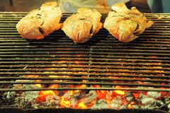 Fish being barbecued on the grill with flames Stock Images